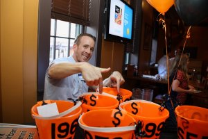 Filling the buckets in the decades race to support YSEF Grant Programs during the Alumni Homecoming event at Holy Hound.